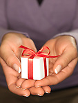 Close up of a woman's hands holding a small white gift box with a red ribbon.
