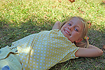 Young girl rests under shade of tree on a sunny day.