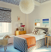 In this child's bedroom the goose-feather pendant light was found in Paris and a colour scheme of identical browns and blues in contrasting designs has been used for the upholstery on the bed, blind and ceiling panels