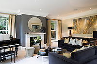 The spacious sitting room is decorated in tones of grey and gold and features a rare piano. Two sofas arranged in front of the fireplace provide plenty of comfortable seating and the steel coffee table and circular mirror above the fireplace add a contemporary note to the otherwise traditionally styled room.