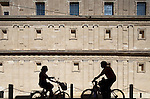 Cyclists in front of Sagrario Church, Constitution Avenue, Seville, Spain