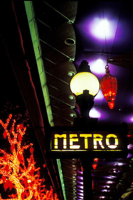 Metro station in Paris at night. The Metro is the rapid transit metro system in Paris. It has become a symbol of the city, noted for its density within the city limits and its uniform architecture influenced by Art Nouveau. The Metro network's sixteen lines are mostly underground and run to 214 km (133 mi) in length. There are 300 stations (384 stops), of which 62 facilitate transfer to another line. Paris has one of the densest metro networks in the world, with 245 stations within 86.9 km2 (34 sq mi) of the City of Paris. Lines are numbered 1 to 14.