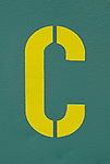 Yellow letter C sprayed on a greyish, green wall.
