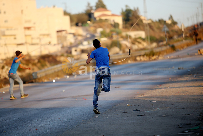 Palestinian protesters use slingshots during clashes with Israeli security forces earby the Jalazoun refugee camp and the Jewish settlement of Beit El, north of Ramallah, after a demonstration in reaction to the death of a Palestinian toddler who was burned in an arson attack by suspected Jewish settlers on two homes in the occupied West Bank on July 31, 2015. Photo by Shadi Hatem