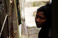A Brazilian girl stands in a shady narrow backstreet in Rocinha, the largest slum in Rio de Janeiro, 28 February 2004.