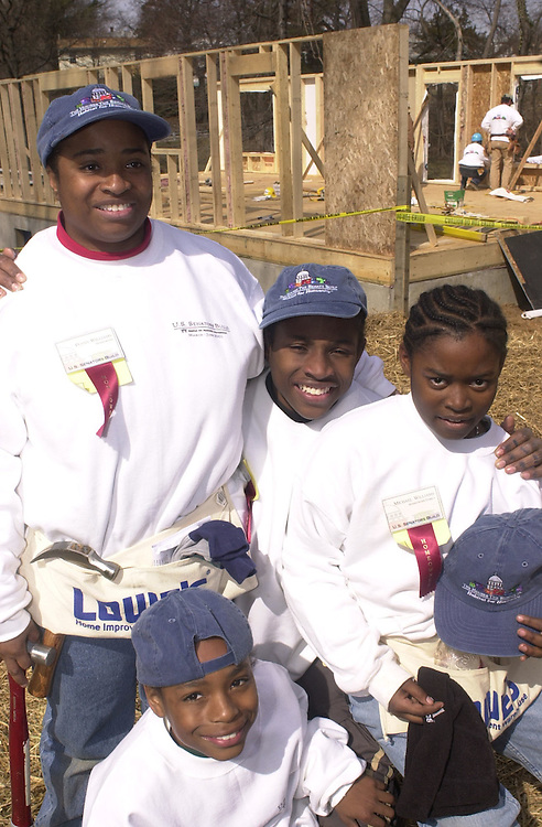 "3hfh030701 -- The Williams family from DC, takes a picture in front of the beginnings of their new home at a Habitat for Humanity event the""U.S. Senators Build"", in which Senators, from both sides, and their spouses worked on raising two house in Capitol Heights, MD."