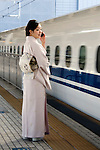 A kimono-clad woman stands on the platform waiting for a shinkansen bullet train in Yokohama, Japan on 03 Feb. 2012. Photographer: Robert GilhoolyA kimono-clad woman stands on the platform waiting for a shinkansen bullet train in Yokohama, Japan on 03 Feb. 2012. Photographer: Robert Gilhooly