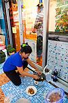 "Thongsuk ""Tip"" Hansawong, a Thai massage therapaist at her shop on Samsen Soi 2. She and her family often eat dinner on the street outside the massage shop."