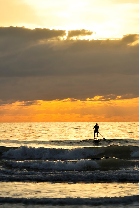 silhouette of a Surfer Paddling Out to the Sunrise