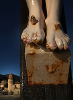 Detail of feet, statue of Christ Crucified, Chapelle St Vincent, 1642, Collioure, France with the Eglise Notre Dame des Anges in the background. Picture by Manuel Cohen.