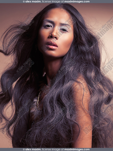 Ethnic beauty portrait of a young woman with beautiful long wavy dark hair