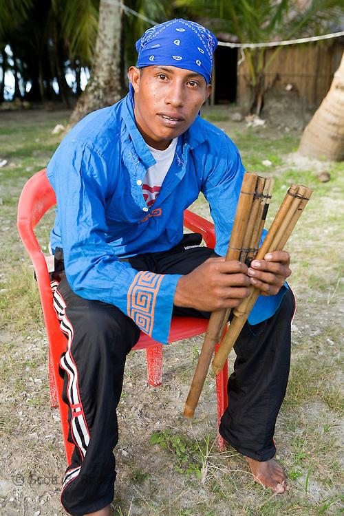 Young Kuna male holding traditional musical pipes before practicing a local dance on Isla Pelikano, San Blas Islands, Kuna Yala, Panama