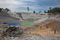 Indonesia - Bangka Island - Rebo - Miners working in Ajong Fang's mine. Once they excavate a pit, often with basic tools like shovels and pickaxes, miners shower the ground with big water pipes. The wet and muddy soil is then pumped through plastic hoses up the washing lines, simple wooden basins constantly irrorated with water, where the ore follows the same cleaning process as in the offshore pontoons. The workers extract 200 kg of pure tin per day from his concession.