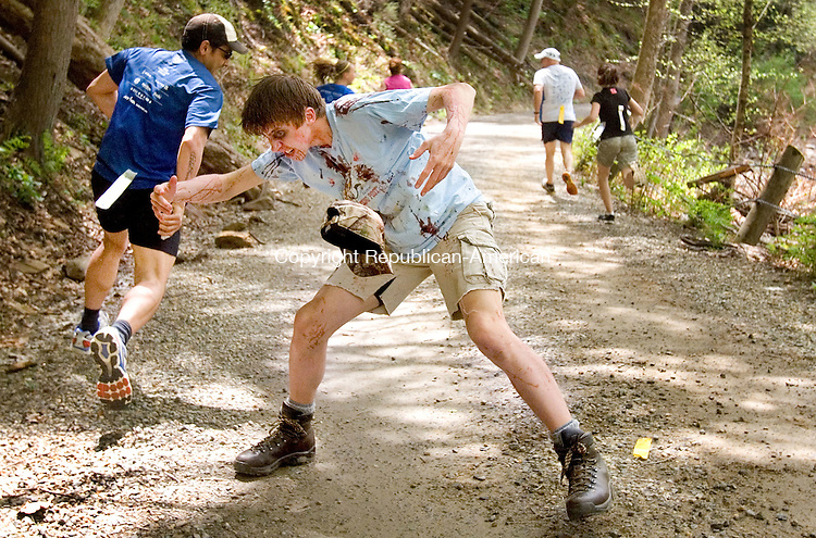WASHINGTON CT. 09 May 2015-050915SV11-Erik Quist, 17, of New Preston dressed as a Zombie attacks runners during the 5K Zombie Run Against Epilepsy at the Steep Rock Preserve in Washington Depot Saturday.<br /> Steven Valenti Republican-American