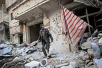 In this Sunday, Dec. 02, 2012 photo, a Syrian resident collect his belongings as he gets back to his home in Amarya neighborhood after the rebel fighters took control of the area over the Syrian army during heavy fighting in Aleppo, the Syrian's largest city. (AP Photo/Narciso Contreras)