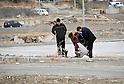 March 11, 2012, Rikuzentakata, Japan - A Japanese family offers prayers on an empty lot where there home was  a year ago in  Rikuzentakata, Iwate Prefecture, some 402 km northeast of Tokyo, on Sunday, March 11, 2012..Memorial ceremonies were held throughout Japan to mark the one year anniversary of the massive earthquake and tsunami that struck the country?fs northeastern region, killing just over 19,000 people and unleashing the world?fs worst nuclear crisis in a quarter century. The quake was the strongest recorded in the nation?fs history, and set off a tsunami that towered more than 65 feet in some spots along the northeastern coast, destroying thousands of homes and wreaking widespread destruction. (Photo by Natsuki Sakai/AFLO) AYF -mis-