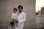 Marsh Arabs. Southern Iraq. Circa 1985. Marsh Arab man with daughter outside his adobe home banks of river Tigris.