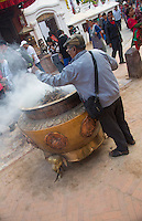 Kathmandu Nepal man wafting incense on himself for good luck. Boudhanath Stupa.