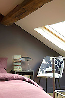 The bedroom is situated on the mezzanine and the bed is tucked under a skylight
