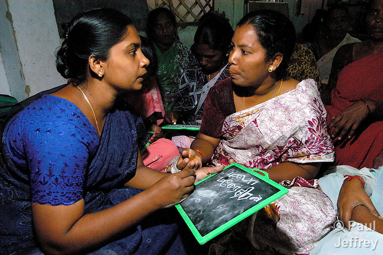 Carlione (left), a Methodist Bible Woman in the village of Bharathiyar Nagar, in the southern Indian state of Tamil Nadu, teaches basic literacy skills to other women in her village.