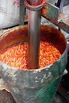 Asia, China, Chongqing. Grinding chili peppers into poweder at local street market in the city of Chongqing.