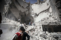 Syrian residents remove the debris from a destroyed building as they look for bodies after an aistrike hits a residential area in Al-Ansari, a neighborhood under control of the rebel fighters in Aleppo, Syria.