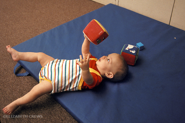 Berkeley CA Baby, eight months old, reaching for soft block with spread-out hand at daycare