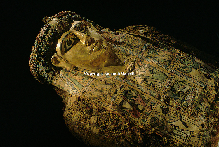 Valley of the Mummies, Gilded Munmmy, with typical Greek spiral curls, Staring eyes joining traditional Egyptian motifs, Bahariya Oasis, Egypt