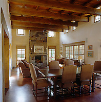 In a contemporary New Mexico house wooden beams, terracotta floor tiles and a stone fireplace have been combined to create an open-plan living/dining area of great rustic charm