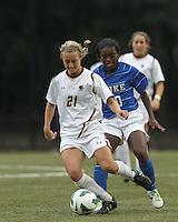 Boston College midfielder Kate McCarthy (21) dribbles as Duke University midfielder Toni Payne (10) pressures.Boston College (white) defeated Duke University (blue/white), 4-1, at Newton Campus Field, on October 6, 2013.