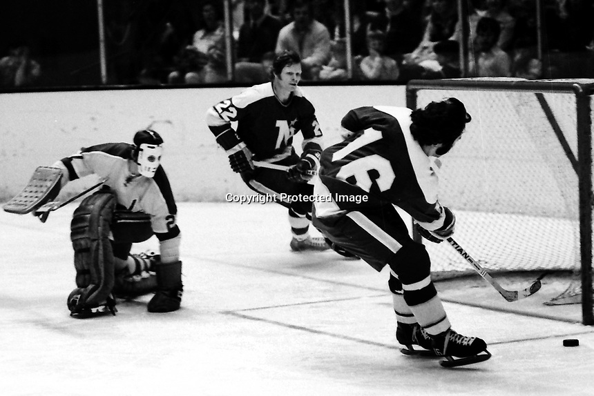 North Stars Jude Drouin and Dennis Hextall against the Seals goalie Gilles Meloche (1975 photo/Ron Riesterer)