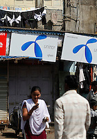 A woman text a message as she walk past advertising for Uninor on a street in Mumbai. Telenor warned it could be forced to reconsider its presence in India if the New Delhi revises the terms of its spectrum licence amid a political scandal over regulation of the Indian telecoms industry.<br /> <br /> Unitech, since renamed Uninor, is one of five companies alleged to have benefited from irregularities that an official audit claimed had cost the Indian government $39bn in lost revenues from spectrum licences. <br /> <br /> Further reading : http://www.ft.com/cms/s/0/f391ebb0-33b4-11e0-b1ed-00144feabdc0.html#axzz1DWW1eUZh
