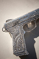 A gun covered in Swarovski crystals, designed by jeweler-to-the-stars Rodrigo Otazu, sits on a table in a photo studio in New York, 8 November 2009.