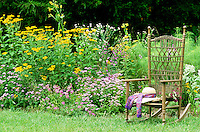 Handwover wicker rocking chair in country garden with a hat and a bouquet in the seat