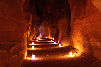 Siq at night lit by candles, Petra, Ma'an, Jordan. The Siq is a 1.2km gorge formed when the earth split by tectonic forces and is the main entrance to Petra. Water channels were carved into the rock on both sides by the Nabateans in the 1st century BC to bring water from springs to the city. Petra was the capital and royal city of the Nabateans, Arabic desert nomads. Picture by Manuel Cohen