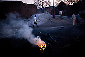 Local residents walk past the coal fires in Borapahari in Jharia, Jharkhand, India. Coal fires rage just below the surface of the ground, making it too hot to walk with naked feet, noxious gases spew up from fissures, making the environment toxic. Residents who live above the furnace make $2 a day collecting small chunks of coal they sell to illegal middlemen. One or two houses collapse annually into vast underground caverns left unfilled by abandoned mining operations. Photo: Sanjit Das