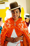 Young Bolivian cholita dressed in bowler hat and manta or shawl,the traditional  indigenous Aymaran clothing, celebrating Bolivian Independence Day in La Paz, Bolivia.