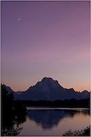 On a calm evening, the sun sets and leaves Oxbow bend in soft pastels of evening in this image from the Grand Tetons and the Rocky Mountains.