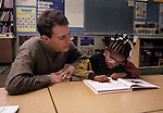 Oakland CA First grade teacher supervising reading of vision impaired student  MR