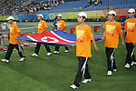 09 August 2008: Olympic volunteers carry the flag of North Korea onto the field, pregame.  The women's Olympic soccer team of Brazil defeated the women's Olympic soccer team of North Korea 2-1 at Shenyang Olympic Sports Center Wulihe Stadium in Shenyang, China in a Group F round-robin match in the Women's Olympic Football competition.