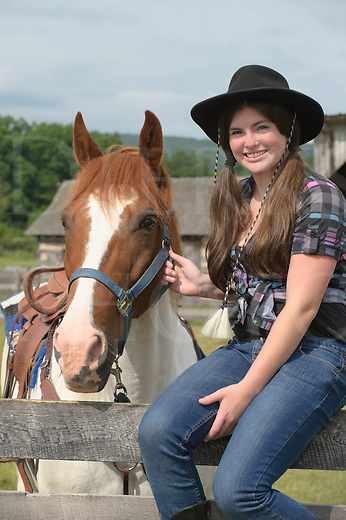 Teen girl sitting on fence and her paint horse, casual western clothing with cowboy hat and hair in pigtails.