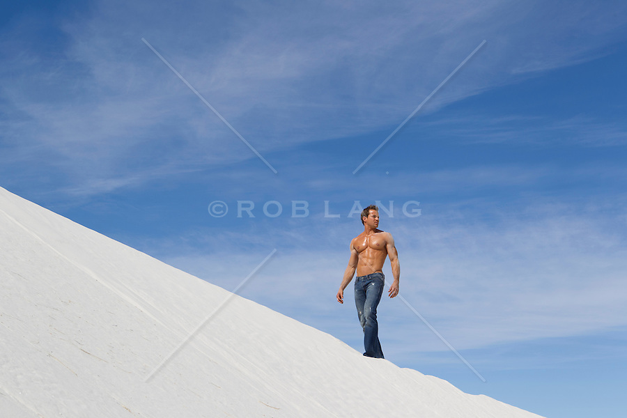 shirtless in shape man wearing jeans standing on a sand dune in New Mexico