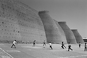 Children play football outside the walls of 'The Ark', the oldest structure in town and once the home of the Emir of Bukhara, in the Old Silk Road trading route city of Bukhara, Uzbekistan