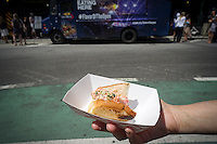 "A foodie displays her sample of a Liberty Pier Seafood Lobster Roll in Madison Square in New York on Monday, August 11, 2014 at the US Open food truck. The US Tennis Association (USTA) is promoting eating at the Open, which has a reputation for serving notoriously over-priced food, with a food truck visiting the city serving gourmet items from celebrity chefs and from the Open's ""Food Village"" Samples include Lobster Roll and David Burke Filet Slider. The US Open runs from Aug. 25 through Sept. 8 in Arthur Ashe Stadium in Queens.  (© Richard B. Levine)"
