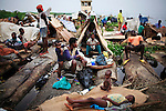 MBANDAKA, DEMOCRATIC REPUBLIC OF CONGO JUNE 30: Francesca Mboyo (c), age 35, prepares to cook for her six children, while traveling   on a boat made of big trees on the Congo River on June 30, 2006 outside Mbandaka, Congo, DRC. The boat traveled with about 150 passengers from Bumba to Kinshasa, a journey of about 1300 kilometers. Francesca traveled from a small rural village outside Bumba to the capital, Kinshasa. The Congo River is a lifeline for millions of people, who depend on it for transport and trade. Passengers slept in the open, with their goats, pigs and other animals. Boat travel is the only option for most people along the river as there?s no roads or infrastructure. Very few can afford to fly in a plane to the capital Kinshasa. During the Mobuto era, big boats run by the state company ONATRA dominated the river. These boats had cabins and restaurants etc. All the boats are now private and are mainly barges that transport goods. The crews sell tickets to passengers who travel in very bad conditions. The conditions on the boats often resemble conditions in a refugee camp. Congo is planning to hold general elections by July 2006, the first democratic elections in forty years. The Congolese and the international community are hoping that Congo will finally have piece and the country will be rebuilt..(Photo by Per-Anders Pettersson/Getty Images)..
