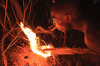 Joseph lights an armful of dried grass to smoke out this colony, which has found refuge in an abandoned termites' nest.