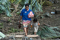 A young woman and her child walk through the debris near their home at Lalomanu, the area worst hit by the tsunami. More than 170 people died when a tsunami triggered by an 8.3 magnitude earthquake hit Samoa and neighbouring Pacific islands on 29/09/2009. Samoa (formerly known as Western Samoa)..