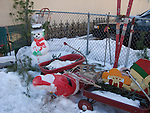 Yard decorations, wagons, skis and plywood cut outs sit in the winter snow.