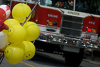 Humorous smiley style yellow ballons and fire engine at paarade.