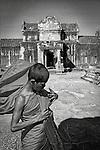 A yung monk adjusts his flowing robe at Angkor Wat Temple, Cambodia